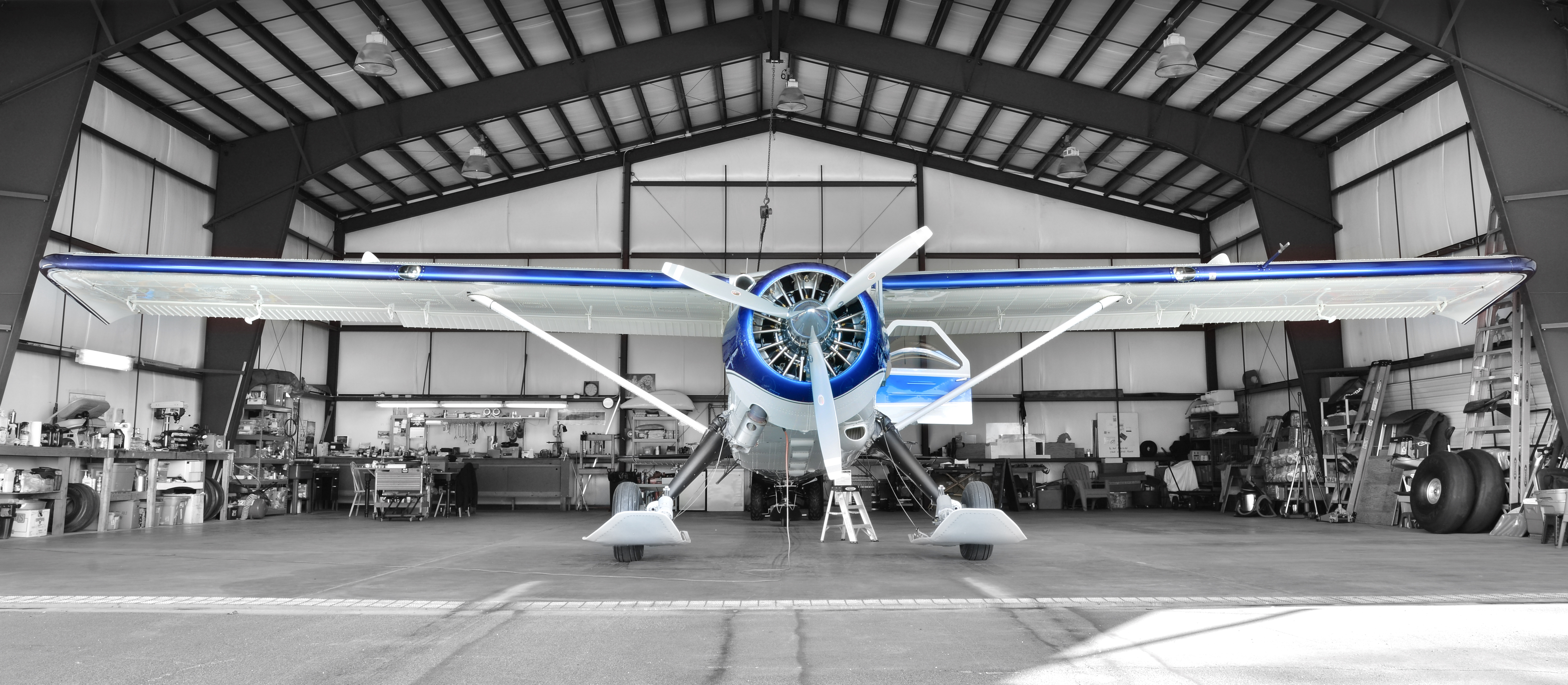 Background image displaying a plane in a hangar.